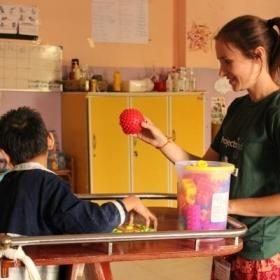 A disabled child does basic exercises using a ball with a student doing an Occupational Therapy internship abroad.